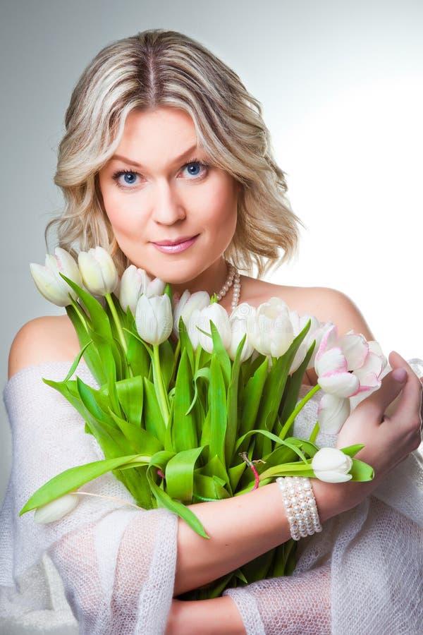 Mooie vrouw met de lentetulpen op grijs stock fotografie