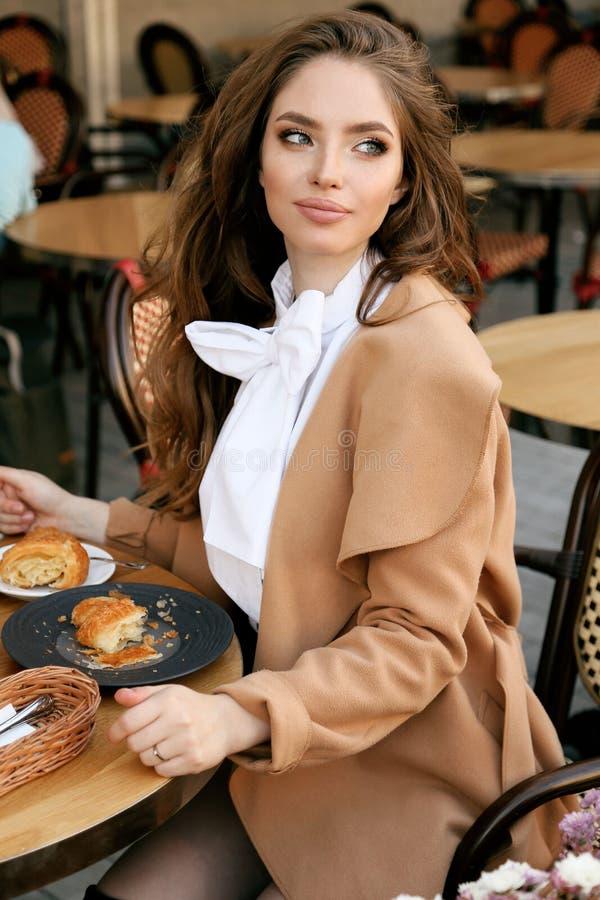 Mooie vrouw met donker haar in elegante uitrustingszitting in koffie stock fotografie