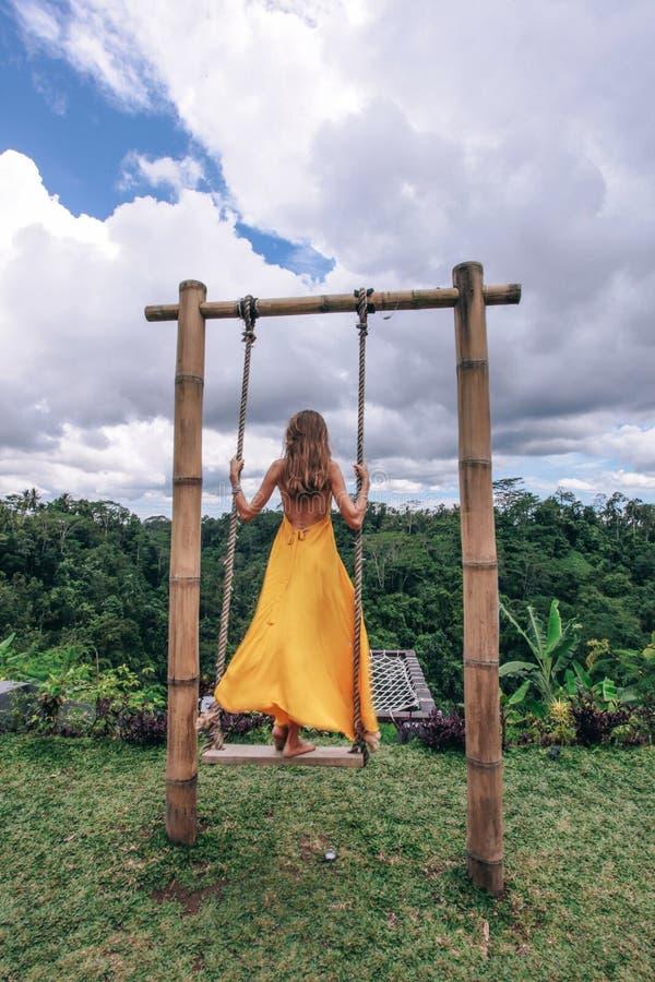 Mooie vrouw met donker haar in het gele kleding stellen op de schommeling met de wildernismening van Bali royalty-vrije stock foto's