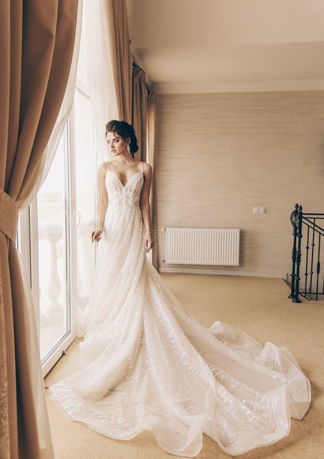 Mooie vrouw met donker haar in luxueuze huwelijkskleding royalty-vrije stock afbeelding