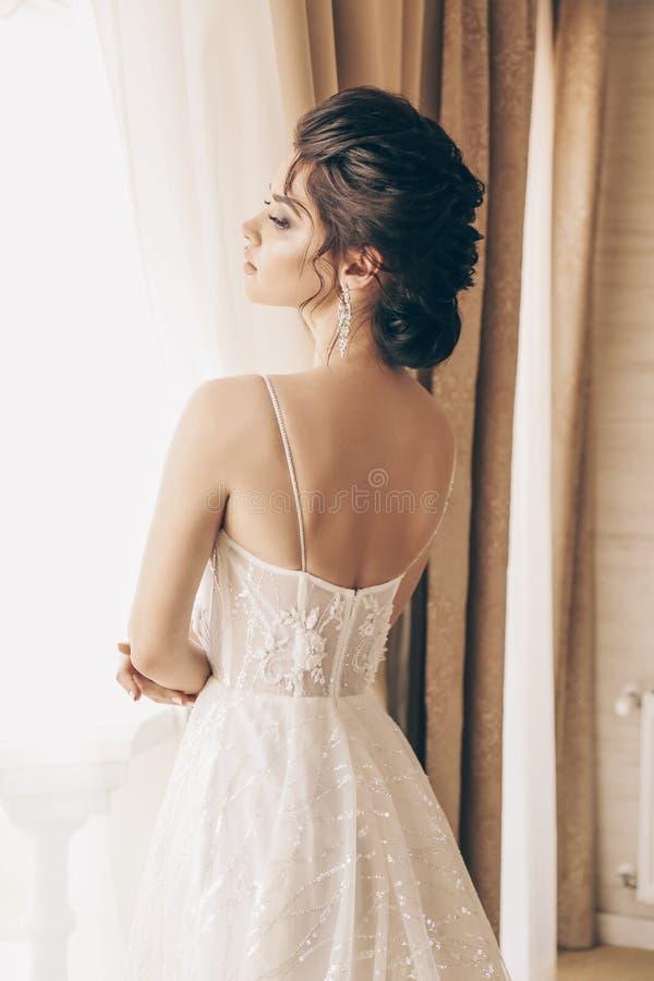 Mooie vrouw met donker haar in luxueuze huwelijkskleding royalty-vrije stock afbeeldingen