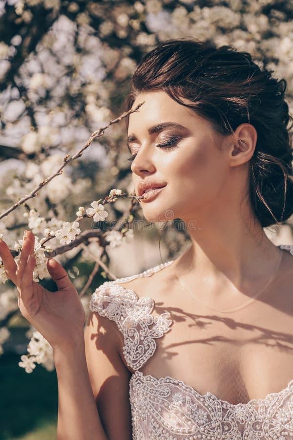 Mooie vrouw met donker haar in luxueuze huwelijkskleding stock foto's