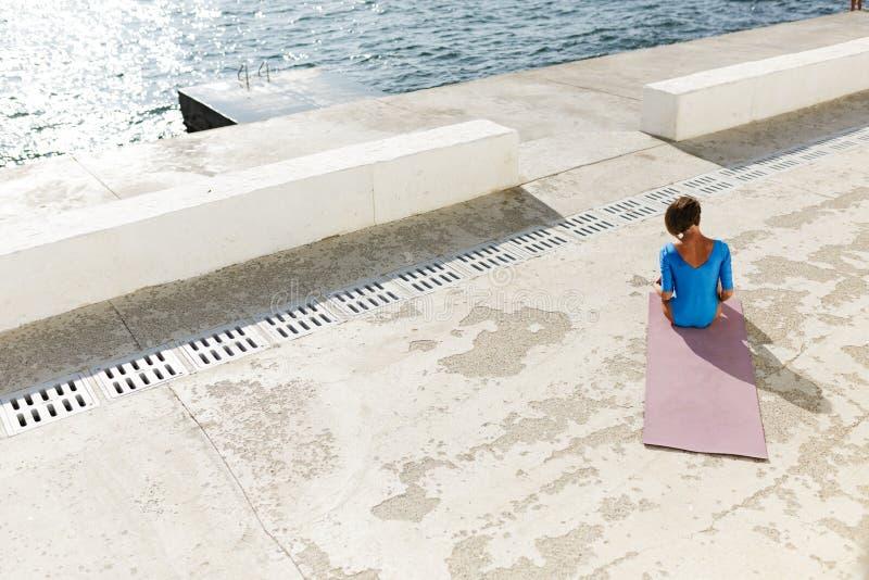 Mooie vrouw met donkere korte haarzitting met haar terug op yogamat en het mediteren door het overzees royalty-vrije stock foto's