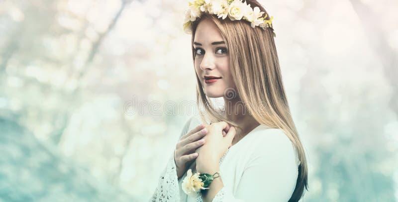 Mooie vrouw met een bloemslinger en een witte kleding stock afbeelding