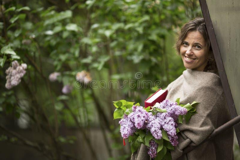 mooie vrouw met een boeket van seringen en een boek in zijn handen, in openlucht onder het groen stock foto