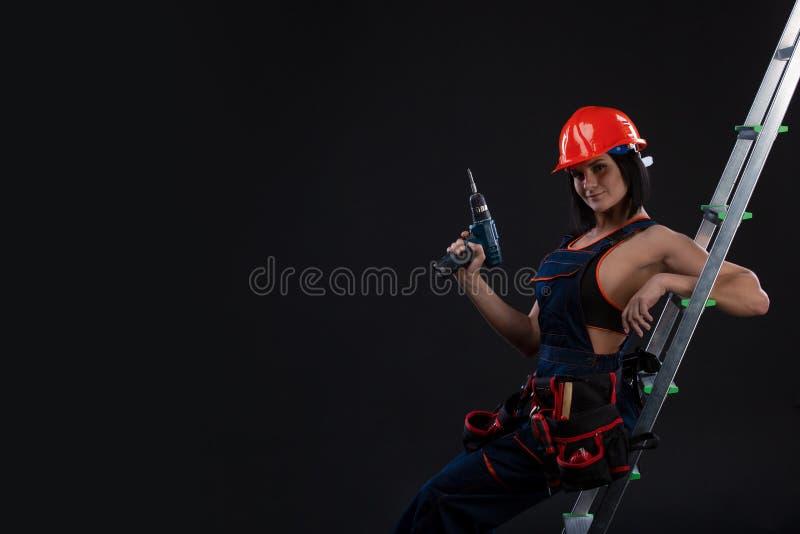 Mooie vrouw met een boor op een ladder klaar om het te gebruiken royalty-vrije stock foto