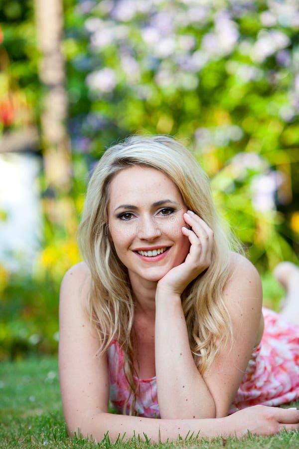 Mooie vrouw met een gelukkige glimlach in de tuin stock foto's