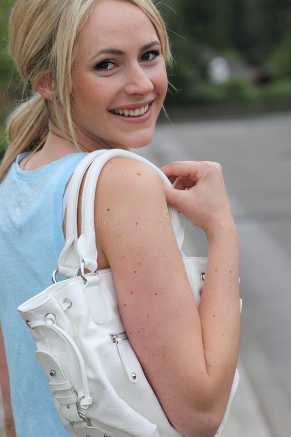 Mooie vrouw met een handtas over haar schouder stock foto's