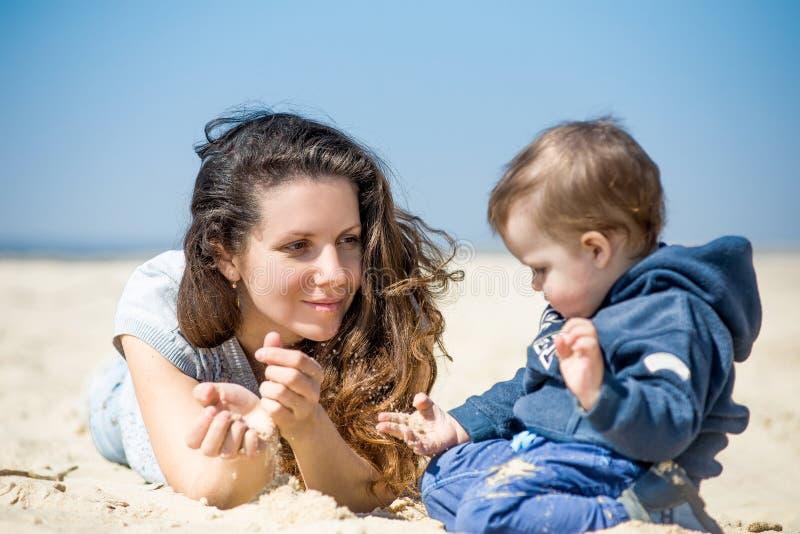 Mooie vrouw met een klein kind die op het strand in de lente rusten stock afbeeldingen