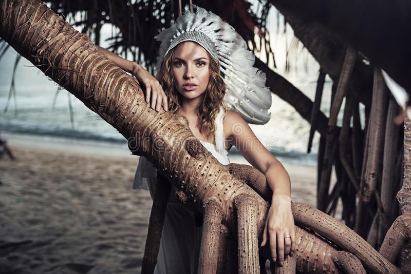 Mooie vrouw met een pluim die tegen de tak leunen stock foto's
