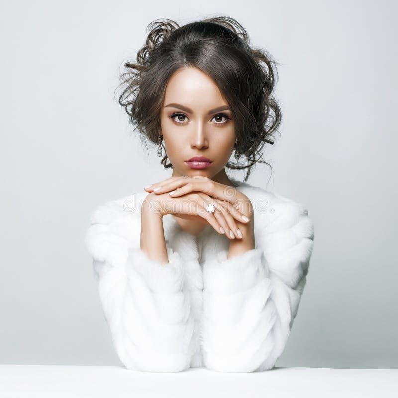 Mooie vrouw met elegant kapsel in witte bontjas royalty-vrije stock foto