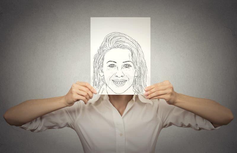 Mooie vrouw met gelukkig zelfportret voor haar gezicht, verbergende ware emoties stock foto