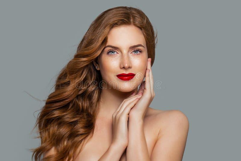 Mooie vrouw met gember krullend op blauwe achtergrond stock afbeeldingen