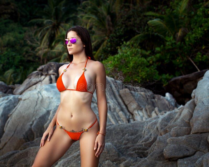 Mooie Vrouw met Geschikt Lichaam in Sexy Bikini, Tropische Klip royalty-vrije stock foto