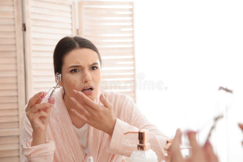 Mooie vrouw met gevallen wimpers en krulspeld dichtbij spiegel stock foto's