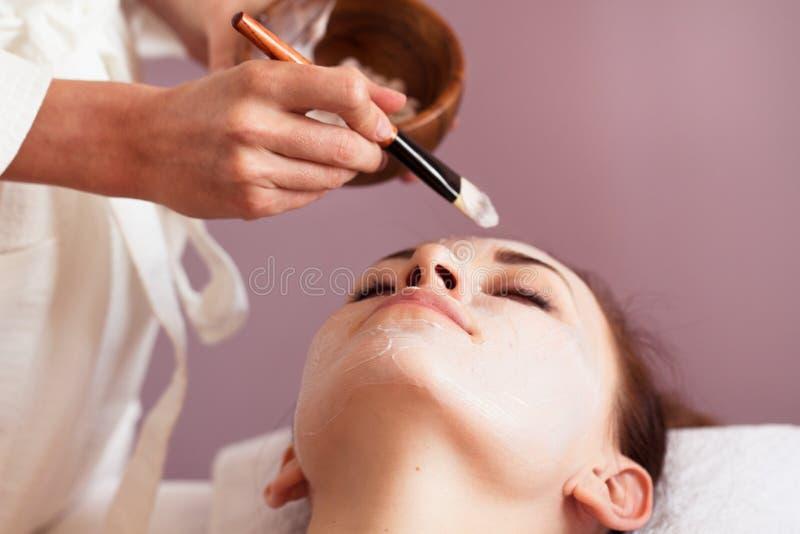 Mooie vrouw met gezichtsmasker bij schoonheidssalon stock afbeeldingen