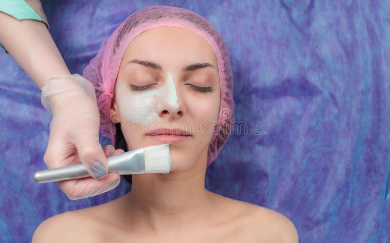 Mooie vrouw met gezichtsmasker bij schoonheidssalon stock fotografie