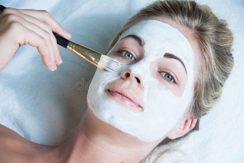 Mooie vrouw met gezichtsmasker bij schoonheidssalon royalty-vrije stock fotografie