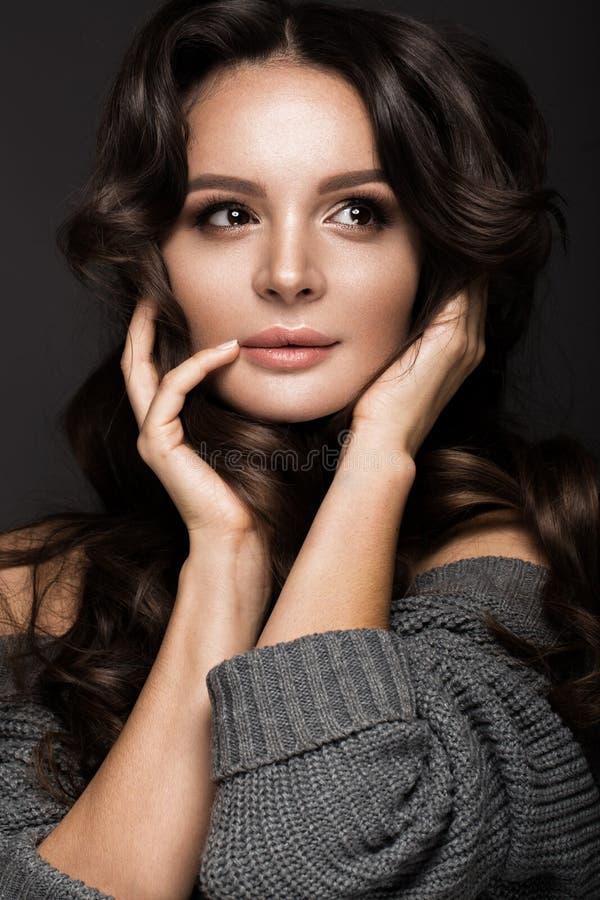 Mooie vrouw met gezonde huid en haarkrullen, die in studio stellen Het Gezicht van de schoonheid royalty-vrije stock afbeelding