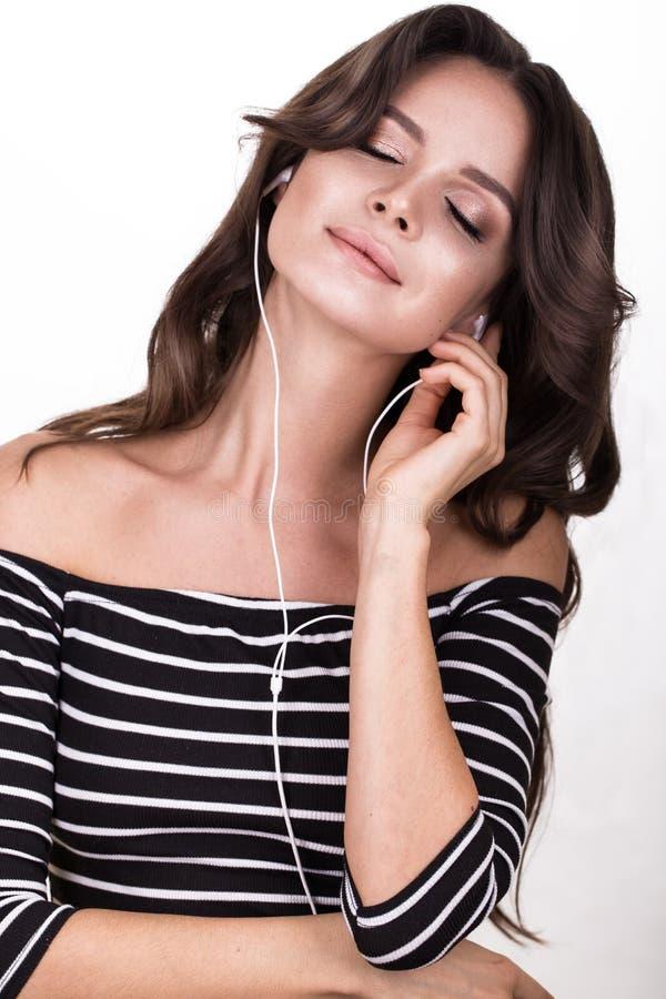 Mooie vrouw met gezonde huid, haarkrullen en hoofdtelefoons, die in studio stellen Het Gezicht van de schoonheid stock afbeeldingen