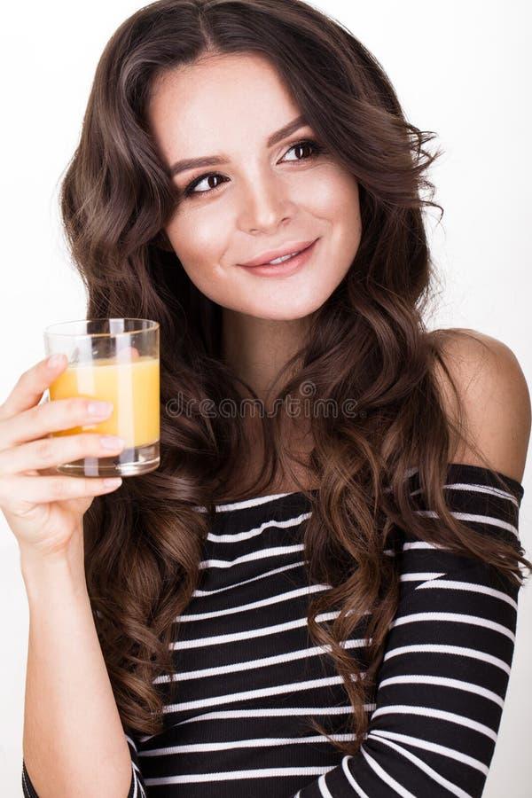 Mooie vrouw met gezonde huid, haarkrullen en jus d'orange, die in studio stellen Het Gezicht van de schoonheid royalty-vrije stock foto