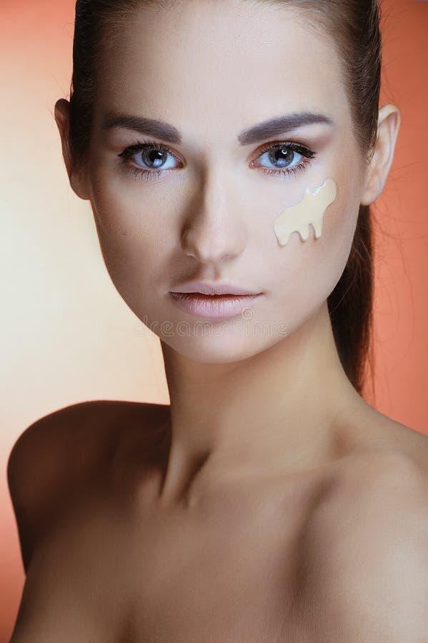 Mooie vrouw met gezondheids verse huid met vrouwelijke make-uproom op haar gezicht stock foto's