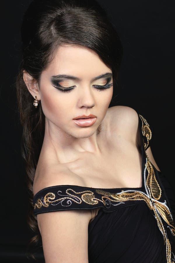 Mooie vrouw met gouden avondsamenstelling stock foto's