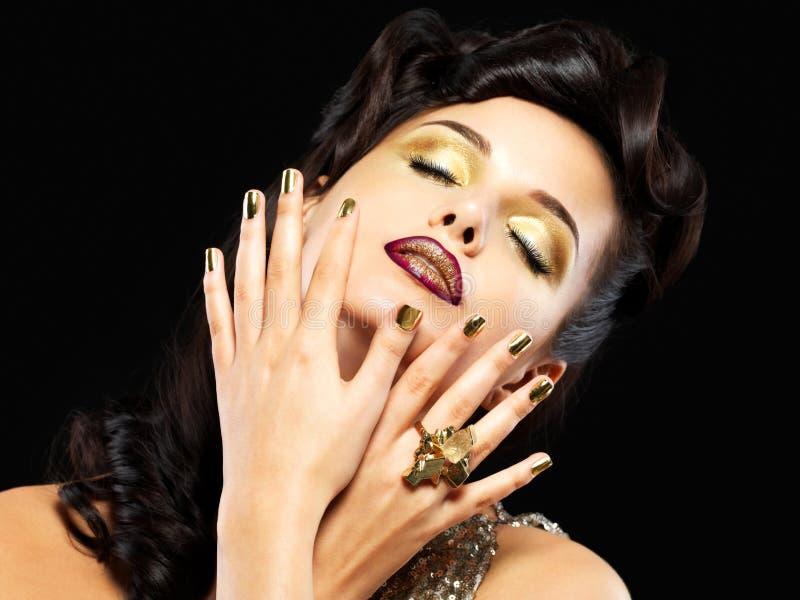Mooie vrouw met gouden spijkers en stijlmake-up royalty-vrije stock foto's