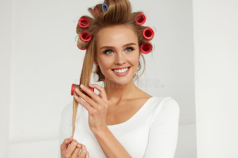 Mooie Vrouw met Haarkrulspelden, Haarrollen op Gezonde Krullend royalty-vrije stock afbeelding