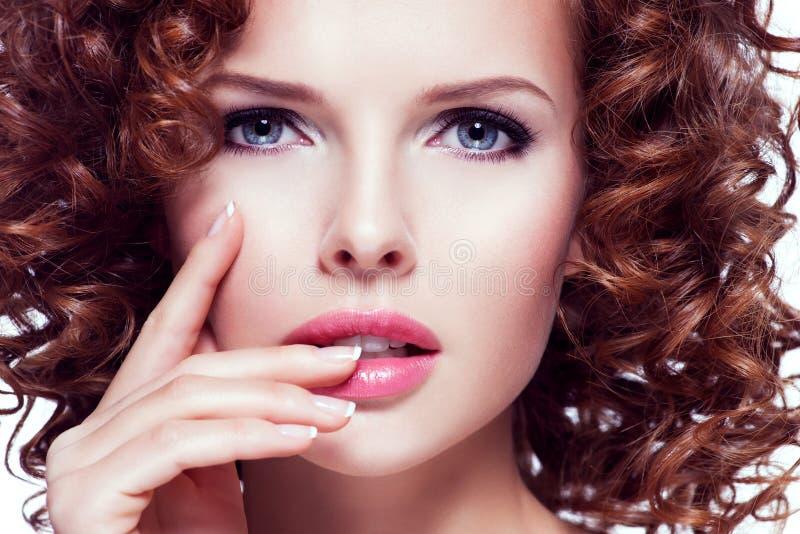 Mooie vrouw met het donkerbruine krullende haar stellen bij studio stock afbeelding