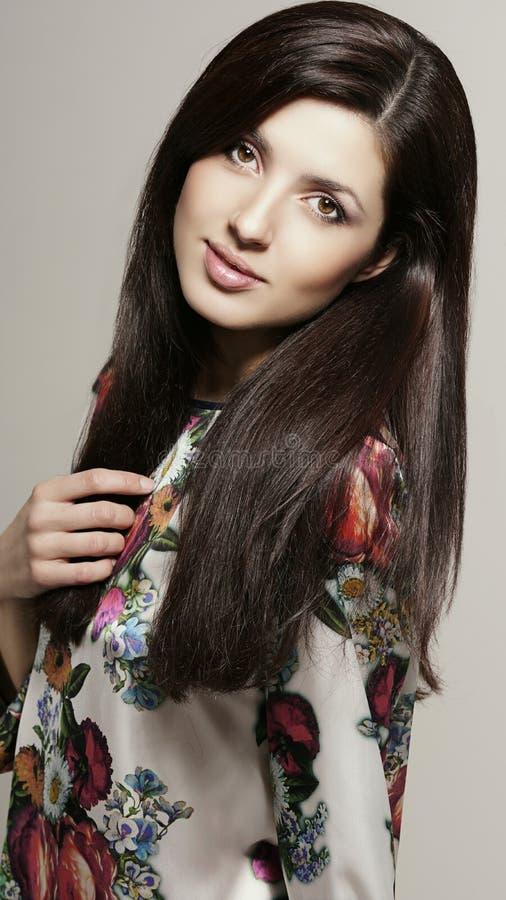 Mooie vrouw met het lange donkere haar stellen in studio royalty-vrije stock afbeeldingen