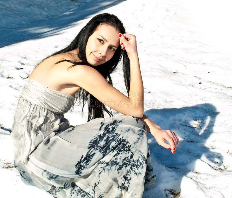 Mooie vrouw met het luchtige kleding stellen in de sneeuw stock afbeeldingen