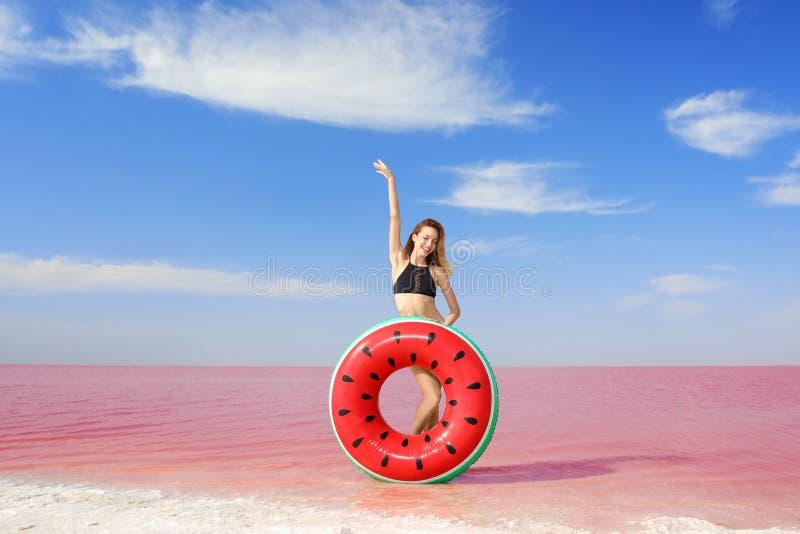 Mooie vrouw met het opblaasbare ring stellen dichtbij roze meer royalty-vrije stock afbeeldingen