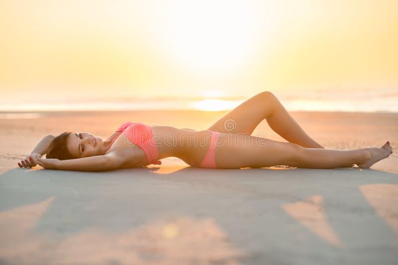 Mooie vrouw met het perfecte lichaam liggen op het strand royalty-vrije stock fotografie