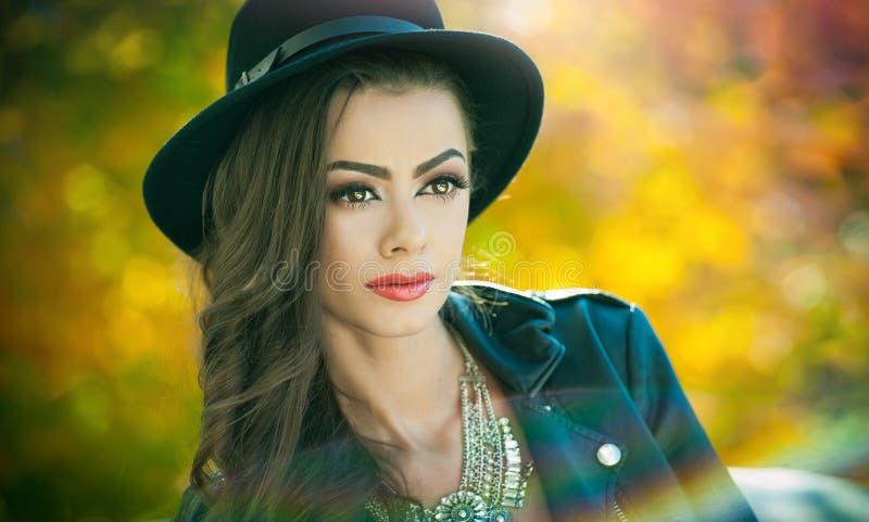 Mooie vrouw met het zwarte hoed stellen in herfstpark Jonge donkerbruine het besteden tijd tijdens de herfst in bos royalty-vrije stock fotografie