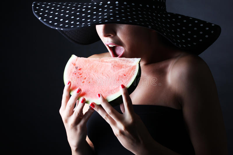 Mooie vrouw met hoed en het eten van watermeloen op zwarte achtergrond royalty-vrije stock foto