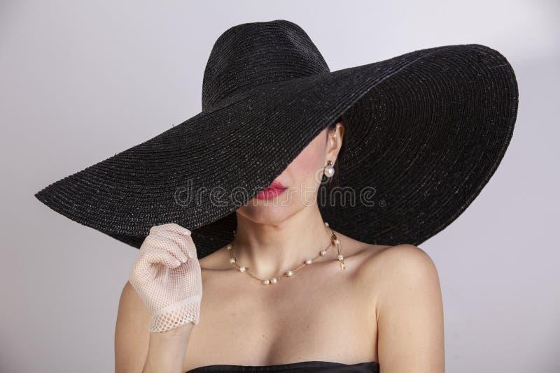 Mooie vrouw met hoed, handschoenen, juwelen en rode lippen Retro manier royalty-vrije stock fotografie