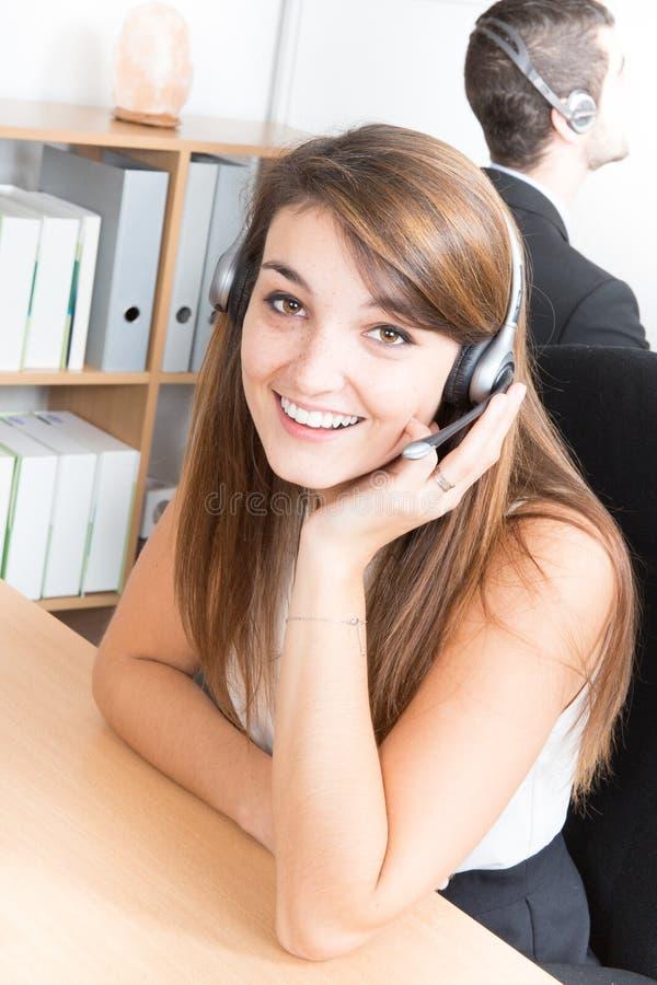 Mooie vrouw met hoofdtelefoon als telemarketer en telefoon het verkopen in bedrijf royalty-vrije stock foto's