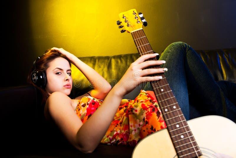 Mooie vrouw met hoofdtelefoons en gitaar stock fotografie