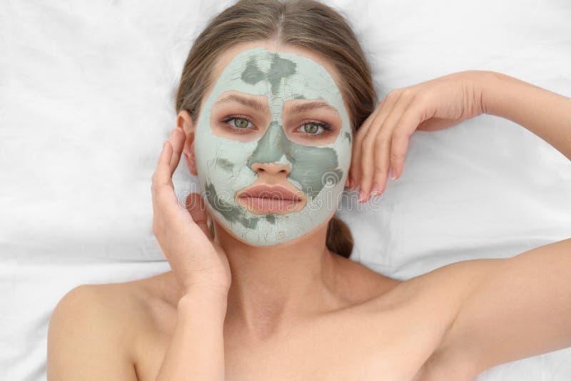 Mooie vrouw met klei gezichtsmasker op witte stof stock foto's