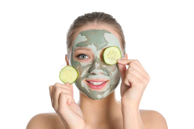 Mooie vrouw met kleimasker op haar de komkommerplakken van de gezichtsholding royalty-vrije stock afbeeldingen