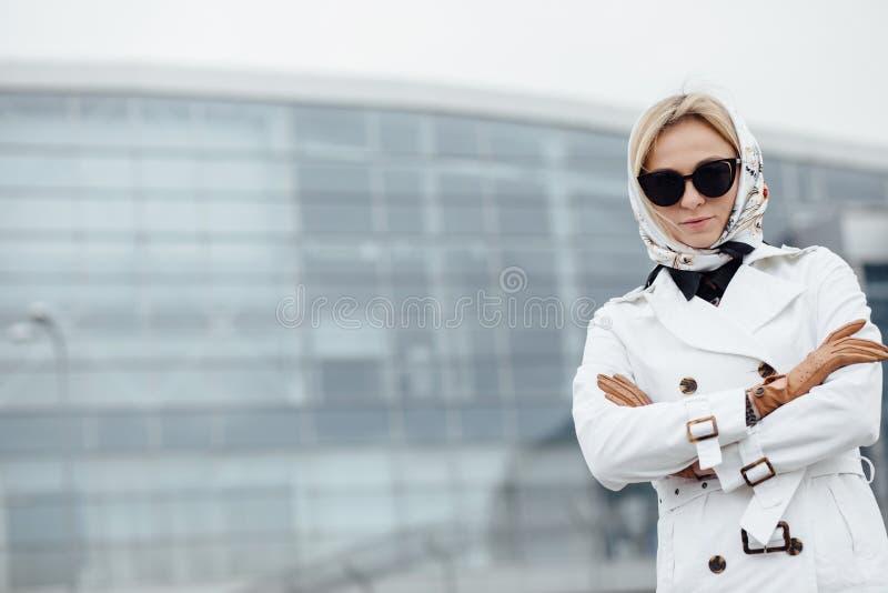 Mooie vrouw met koffiekop dichtbij de bureaubouw royalty-vrije stock afbeelding