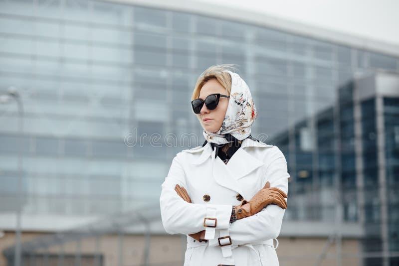 Mooie vrouw met koffiekop dichtbij de bureaubouw stock fotografie