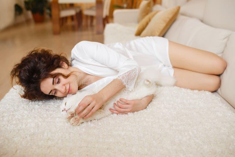 Mooie vrouw met krullend haar in een witte zijdepeignoir vroeg in de ochtend die met witte pluizige kattenzitting spelen op bank royalty-vrije stock afbeeldingen