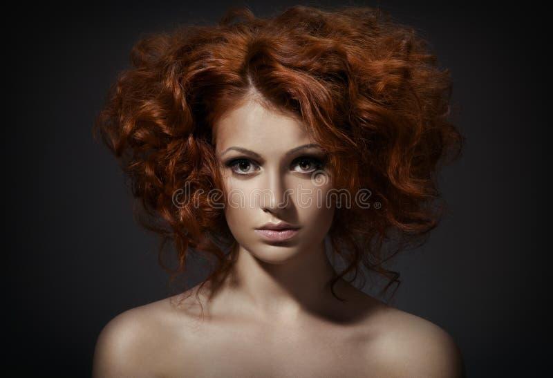 Mooie vrouw met krullend kapsel op donkere achtergrond stock foto's