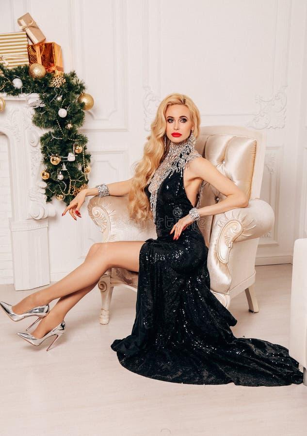 Mooie vrouw met lang blond haar in het elegante kleding stellen dichtbij verfraaide Kerstboom stock foto's