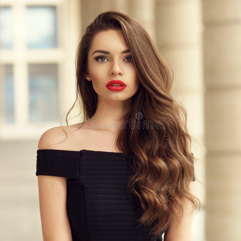 Mooie vrouw met lang donkerbruin krullend haar stock fotografie