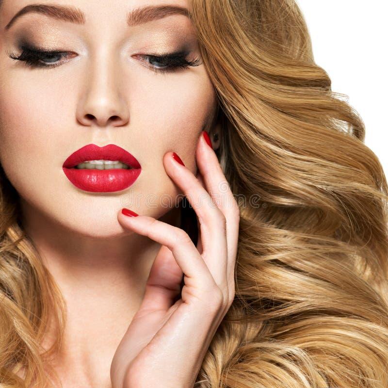 Mooie vrouw met lang haar en rode spijkers royalty-vrije stock foto's