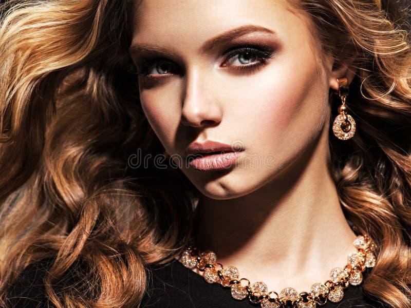 Mooie vrouw met lang krullend haar en gouden juwelen stock foto's