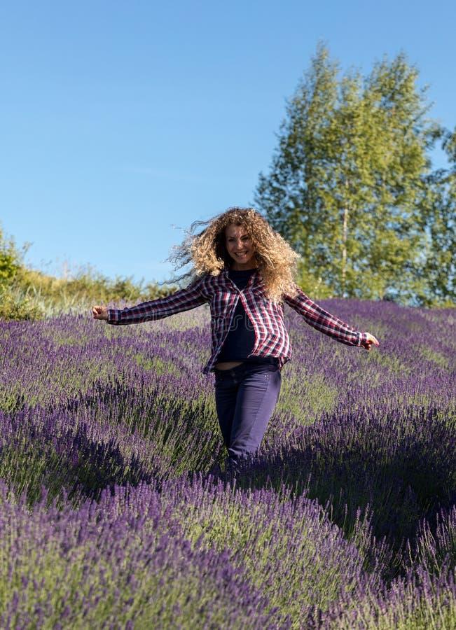 Mooie vrouw met lang krullend haar in het midden van een lavendelgebied in bloei Ostrow dichtbij Krakau, Polen royalty-vrije stock foto's